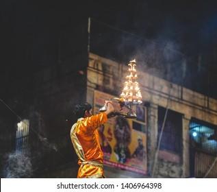 A priest (pandit) performing the rituals of the Shri Maha Ganga Aarti (Ganga Prayer) during evening hours on the banks of the River Ganga in Varanasi (Kashi, Banaras), in Uttar Pradesh, India