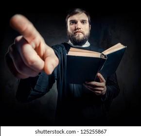 Priest with Prayer book against dark background