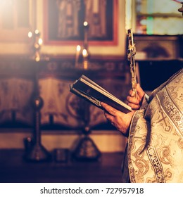 Priest praying in the church holding holly bible and cross