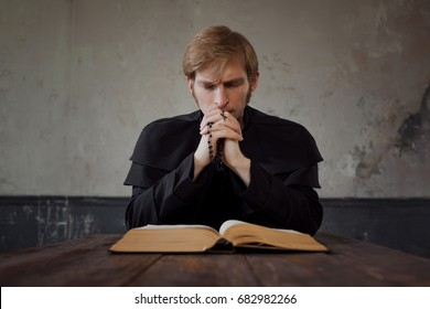 Priest praying to God. Handsome young catholic priest read the Bible