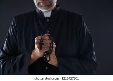 Priest praying hands with rosary beads male