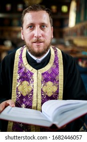 A priest prays in the church reading from the holy book