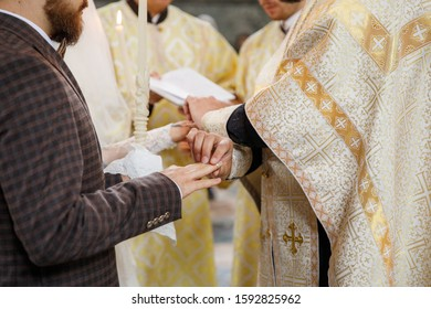 Priest puts on ring on brides finger during church wedding ceremony. Exchange of rings. Horizontal view. Marriage concept.