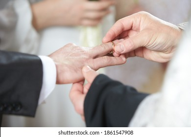 Priest puts on ring on brides and grooms finger during church wedding ceremony. Exchange of rings. Marriage concept. Wedding ceremony, bride, groom, exchanging rings