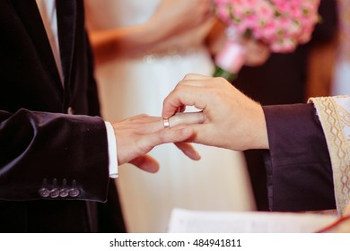 Priest puts a wedding ring on groom's hand in a church
