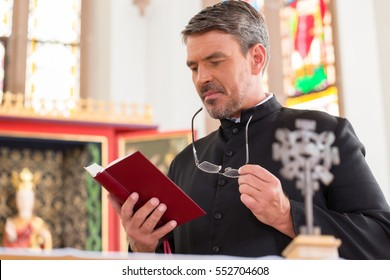 Priest reading bible in church standing at altar