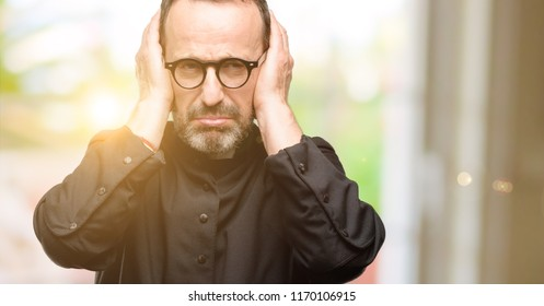 Priest religion man covering ears ignoring annoying loud noise, plugs ears to avoid hearing sound. Noisy music is a problem.