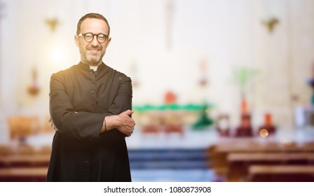 Priest religion man with crossed arms confident and happy with a big natural smile laughing at church