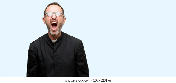 Priest religion man stressful, terrified in panic, shouting exasperated and frustrated. Unpleasant gesture. Annoying work drives me crazy isolated over blue background