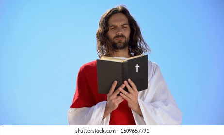 Priest in robe reading Holy Bible, closing eyes to pray, Christian theology