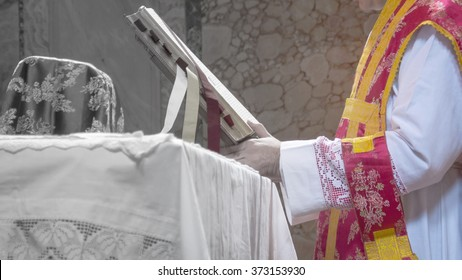 A priest saying the traditional extraordinary tridentine latin rite of the Catholic latin mass. Artistic black and white/color gradient.