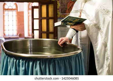 the priest says a prayer over the font, the Bible in the hands of the priest, the sacrament of baptism, the Orthodox tradition