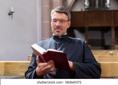 Priest sitting in church reading the bible