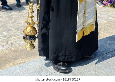 A priest swings a thurible on missal. Orthodox priest with hand censer during worship service. Censer used during liturgy. Man swinging chain censer.