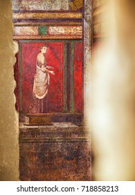 A priestess fresco on a wall of Villa dei Misteri in Via at Ruins of Pompeii. The city was an ancient Roman city destroyed by the volcano Vesuvius. Pompei, Campania, Italy.