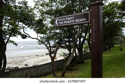 The Priest's Beach sign in English and Irish language off the Promenade directing visitors to one of the beaches in Blackrock village, Dundalk, County Louth.