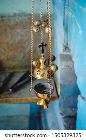 A priest's censer hangs on an old stove in the church. Golden censer with burning charcoal inside. Close-up. Service in  orthodox church concept. Worship.