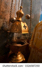 A priest's censer hangs on an old wall in the Orthodox Church. Copper incense with burning coal inside. Service in the concept of the Orthodox Church. Adoration.
