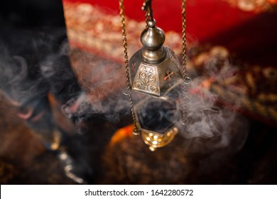 A priest's censer hangs on an old wall in the Orthodox Church. Copper incense with burning coal inside. Service in the concept of the Orthodox Church. Adoration