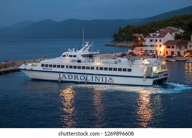 Prigradica/Korcula island/Croatia-September 12, 2018 In the night time Catamaran Novalja, ferry operator Jadrolinija leaves the village of Prigradica port.