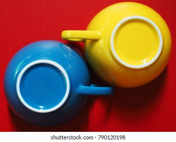 Primary colors concept red background with blue-yellow coffee cups. (Top view, close-up, selective focus)