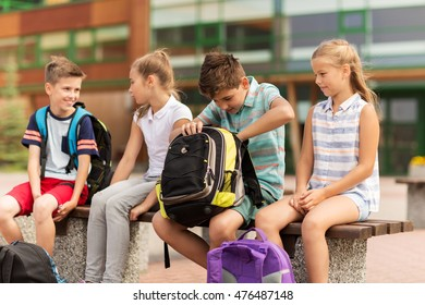 primary education, friendship, childhood, communication and people concept - group of happy elementary school students with backpacks sitting on bench outdoors
