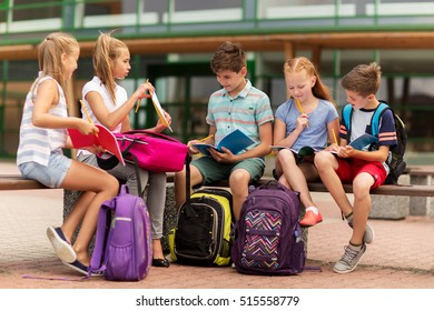 primary education, friendship, childhood, communication and people concept - group of happy elementary school students with backpacks and notebooks sitting on bench outdoors