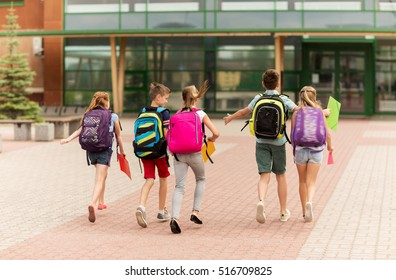 primary education, friendship, childhood and people concept - group of happy elementary school students with backpacks running outdoors