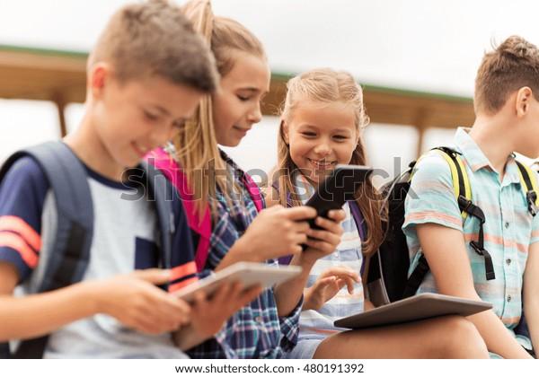 educación primaria, amistad, niñez, tecnología y concepto de personas - grupo de felices estudiantes de primaria con mochilas sentadas en el banco y hablando al aire libre