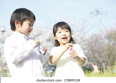 Primary Japanese boy and Japanese girl playing with the soap bubbles
