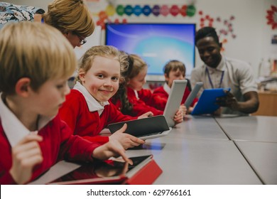 Primary school children are in the classroom, learning about and using digital tablets. One of the girls is smiling at the camera.
