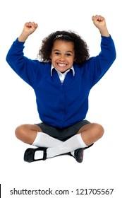 Primary school girl grinding her teeth in excitement. Sitting on floor with crossed legs.