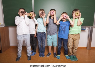 primary school kids looking through donuts in front of blackboard in a classroom