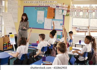 Primary school kids raising hands in class to answer teacher