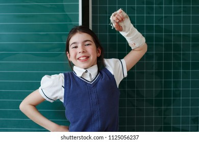 Primary school student on the background of the blackboard with orthosis on his hand. Smiling, raising her hand up. a cast on his arm