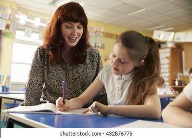 Primary school teacher helping with classwork at girlâ??s desk