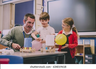 Primary school teacher is helping two of his students with a STEM project. They are building something using recycled items and crafts equipment.
