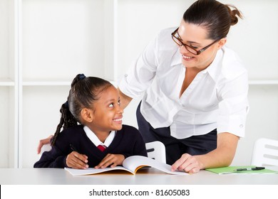 primary school teacher and pupil in classroom