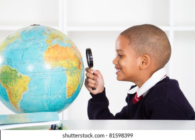 primary schoolboy using magnifying glass looking at globe