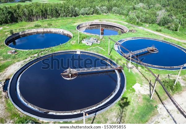 Primärer Abwasserprozess, der durch große kreisförmige Tanks mit mechanisch angetriebenen Abfällen fließt