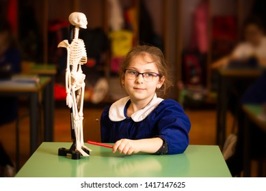 Primary student in the classroom, elementary scool age caucasian girl during interrogation on lesson of biology. School and education concept. Selected focus.