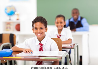 primary students and teacher sitting in classroom