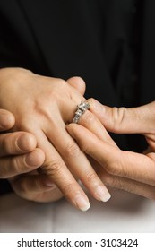 Prime adult Asian male putting engagement ring on female's hand.