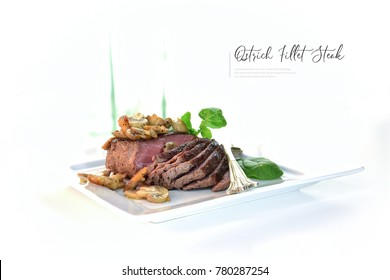 Prime osterich fillet steak flash pan fried with sauteed garlic mushrooms, spinach and watercress salad. Generous accommodation for copy space.