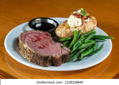 prime rib meal served on a plate with a loaded potato and green beans with a side of a jus