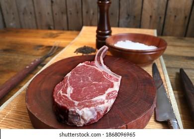 Prime Rib. Raw Rib Eye steak with bone for barbecue. On wooden background