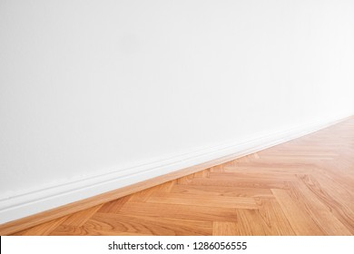 primed white wall and wooden parquet floor - apartment interior background  -