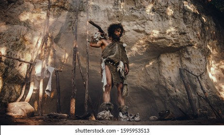 Primeval Caveman Wearing Animal Skin Holds Stone Tipped Hammer Looks Around Prehistoric Forest, Ready to Hunt Animal Prey. Neanderthal Going Hunting into the Jungle.