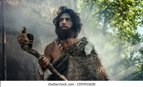 Primeval Caveman Wearing Animal Skin Holds Stone Tipped Hammer Comes out of the Cave and Looks Around Prehistoric Landscape, Ready to Hunt Animal Prey. Neanderthal Going to Hunt in the Jungle