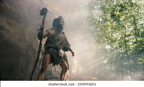 Primeval Caveman Wearing Animal Skin Holds Stone Hammer Stands Near Cave and Looks Around Prehistoric Landscape, Ready to Hunt Animal Prey. Neanderthal Going Hunting into Jungle. Low Angle Shot